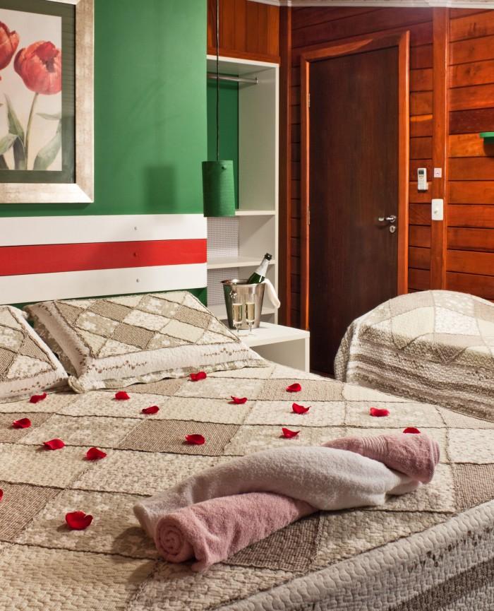 Suíte Master com cama de casal com decoração romântica, taça de vinho, champanhe e pétalas de rosa