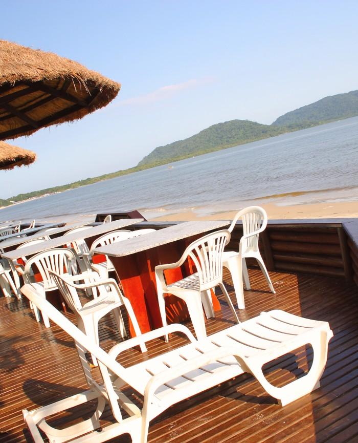 Deck da Pousada Pôr do Sol com cadeira de praia, mesas e cadeiras do restaurante