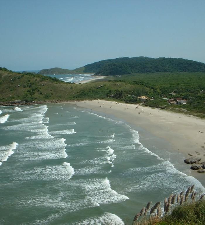 Foto da Praia Grande sobre o morro do Farol, ondas do mar à esquerda e praia com areia à direita